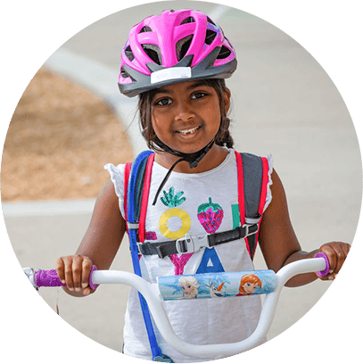 A smiling girl riding a bike